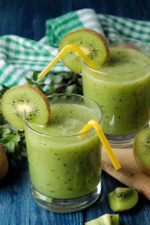 Kiwi smoothies in a glass next to fresh kiwi slices on a blue wooden table. fruit drink royalty free stock photo