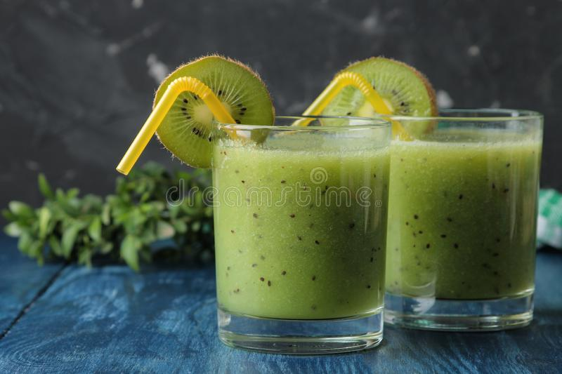 Kiwi smoothies in a glass next to fresh kiwi slices on a blue wooden table. fruit drink stock photography