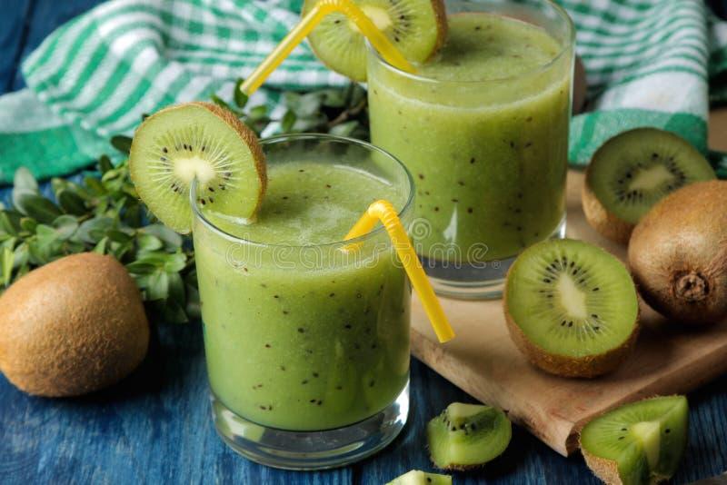 Kiwi smoothies in a glass next to fresh kiwi slices on a blue wooden table. fruit drink royalty free stock photos