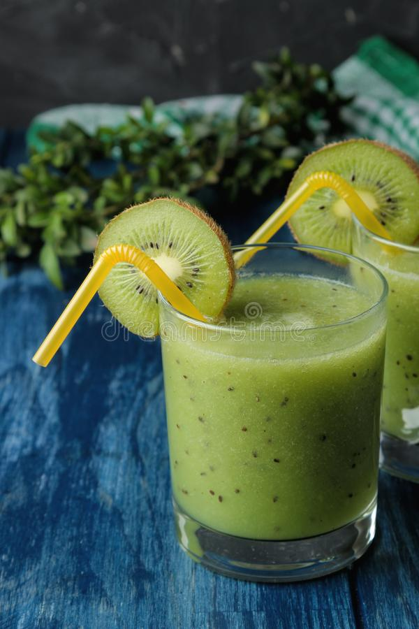 Kiwi smoothies in a glass next to fresh kiwi slices on a blue wooden table. fruit drink royalty free stock image