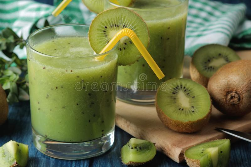 Kiwi smoothies in a glass next to fresh kiwi slices on a blue wooden table. fruit drink royalty free stock photography