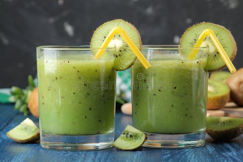 Kiwi smoothies in a glass next to fresh kiwi slices on a blue wooden table. fruit drink stock photos
