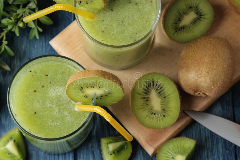 Kiwi smoothies in a glass next to fresh kiwi slices on a blue wooden table. fruit drink. top view royalty free stock photo