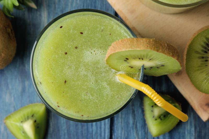 Kiwi smoothies in a glass next to fresh kiwi slices on a blue wooden table. fruit drink. top view royalty free stock image