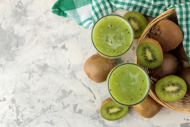 Kiwi smoothies in a glass next to fresh kiwi slices on a light marble table. fruit drink. top view. free space stock photo