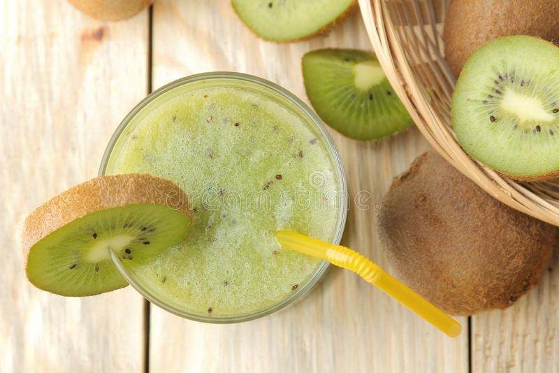 Kiwi smoothies in a glass next to fresh kiwi slices on a natural wooden table. top view royalty free stock photos