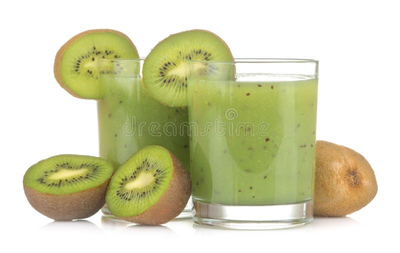 Kiwi smoothies in a glass next to fresh kiwi slices on a white isolated background. fruit drink royalty free stock images