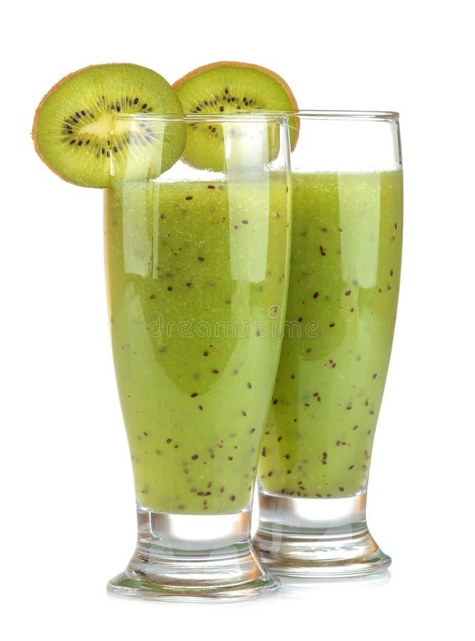 Kiwi smoothies in a glass next to fresh kiwi slices on a white isolated background. fruit drink. Kiwi smoothies in a glass next to fresh kiwi slices on a white stock image