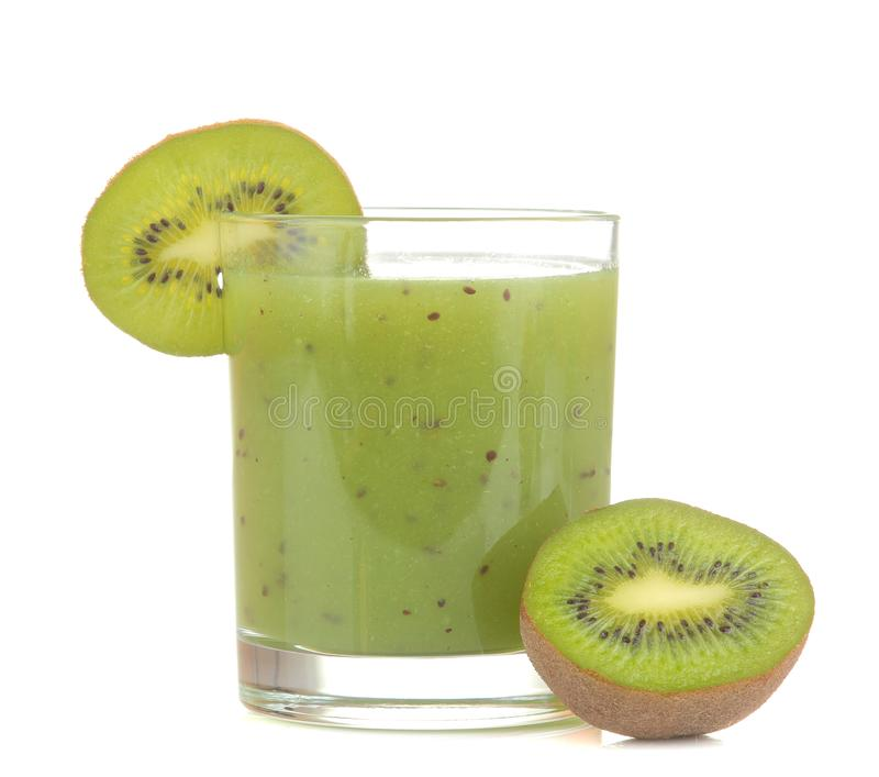Kiwi smoothies in a glass next to fresh kiwi slices on a white isolated background. fruit drink royalty free stock photo