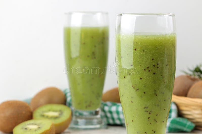 Kiwi smoothies in a glass next to fresh kiwi slices on a light marble table. fruit drink royalty free stock photos
