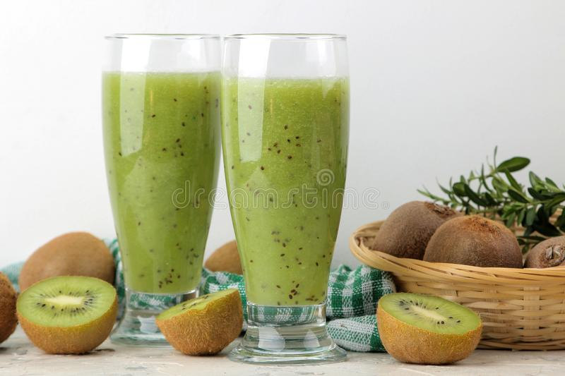 Kiwi smoothies in a glass next to fresh kiwi slices on a light marble table. fruit drink stock photography