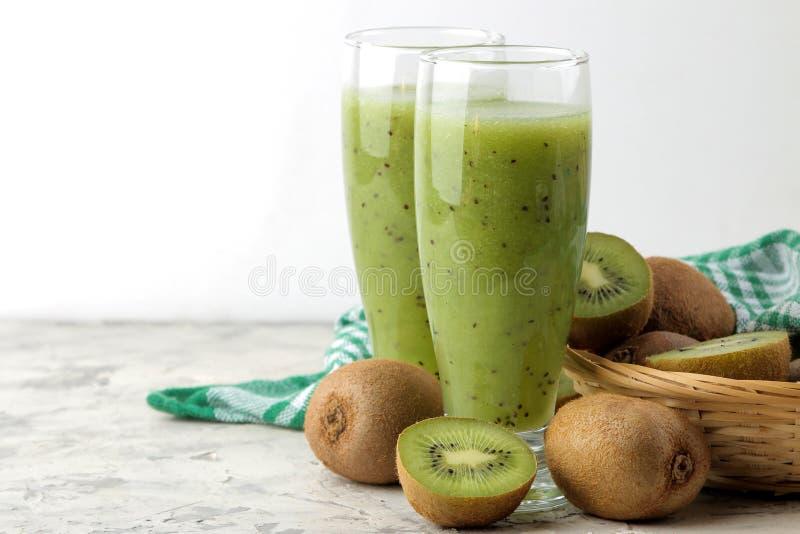 Kiwi smoothies in a glass next to fresh kiwi slices on a light marble table. fruit drink stock photos