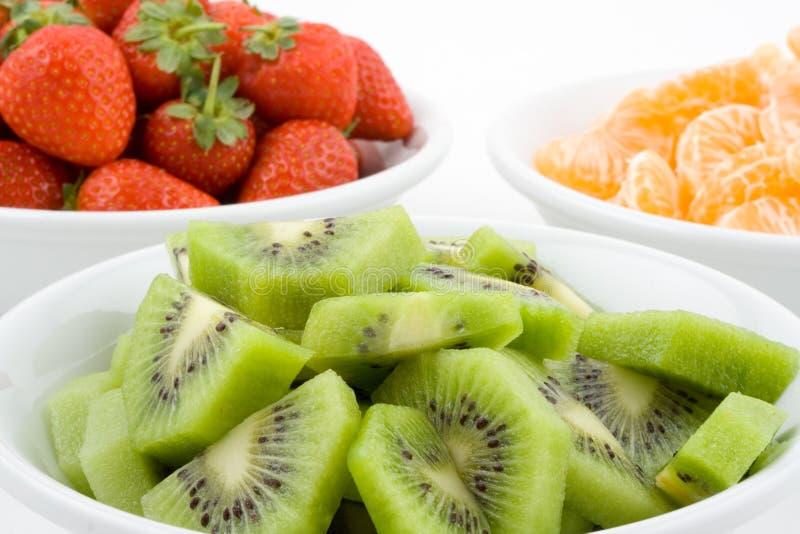Kiwi, strawberry and mandarine, tangerine in white bowls royalty free stock photography