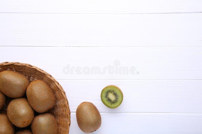 Kiwi in un canestro su fondo bianco fotografie stock
