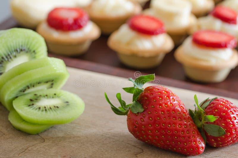 Kiwi und Erdbeere auf der Front, kleine Tartlets verziert mit stockfotos