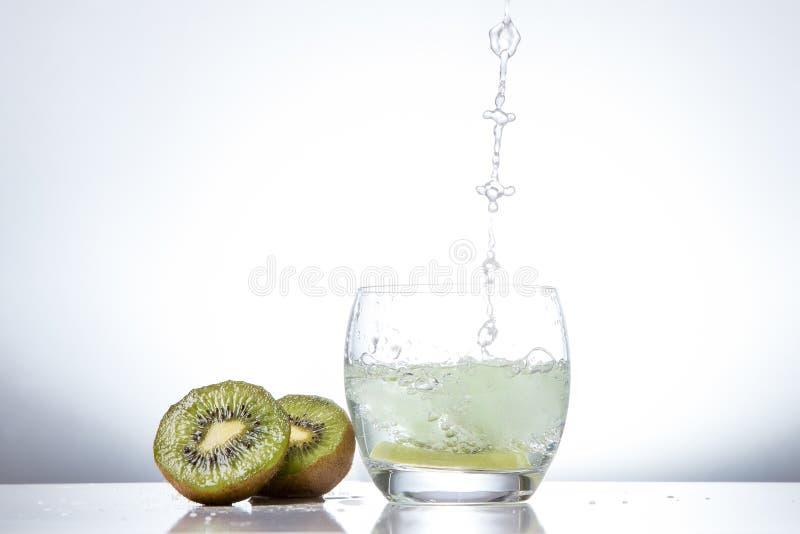Kiwi w szkle i pluśnięciach woda Smakowity i zdrowy jedzenie fotografia royalty free