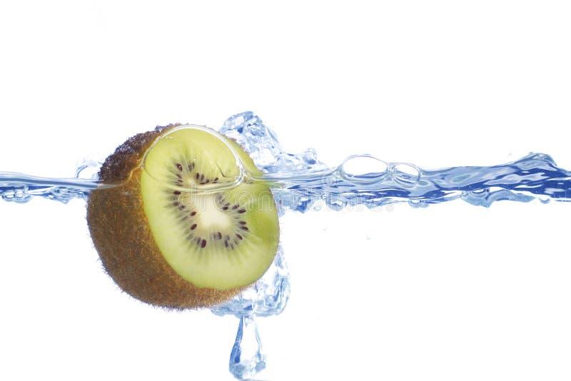 Kiwi in water. Drop green kiwi in water royalty free stock images