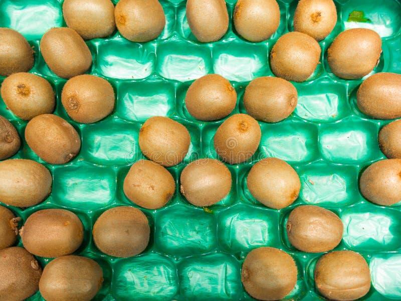 Kiwier gör grön den plast- asken i supermarket som matbakgrund. Detaljhandel. royaltyfria foton
