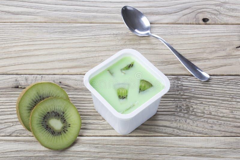 Kiwijoghurt im Plastikkasten mit Löffel auf Tabelle lizenzfreies stockfoto