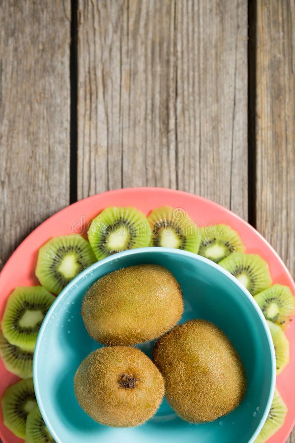 Kiwis arranged in bowl and plate on wooden table stock photography