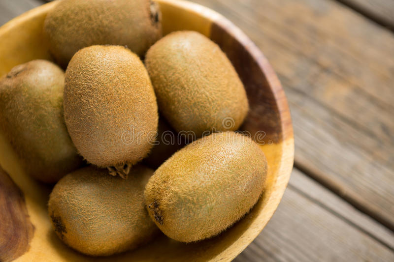 Kiwis in bowl on wooden table stock images