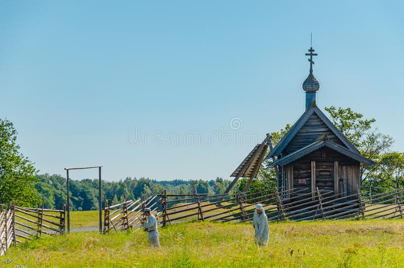 Kizhi Island, Russia -07.19.2018: Peasants mow grass in the field near the church. Reconstruction of 18th century village life.  royalty free stock images