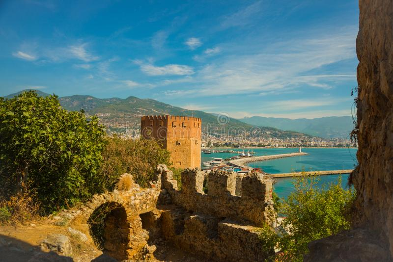 Kizil Kule tower. City view from the top of the fortress wall: Red tower, port, lighthouse, ships, pier, mountains, sea. Alanya. Kizil Kule tower. City view royalty free stock photography