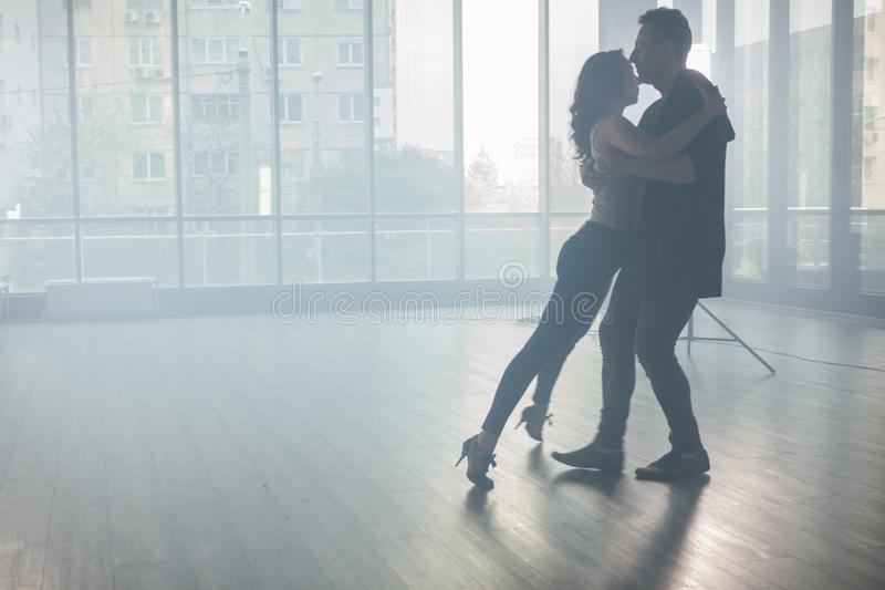 Kizomba dancers showing their passion for dancing kizomba in front a dancing room with big windows in the background. Passionate dancers royalty free stock images