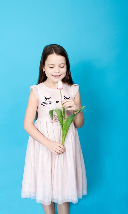 klä flickapinken Flickan tar tulpan i henne händer royaltyfri foto
