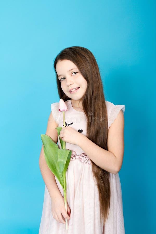 klä flickapinken Flickan tar tulpan i henne händer royaltyfria foton