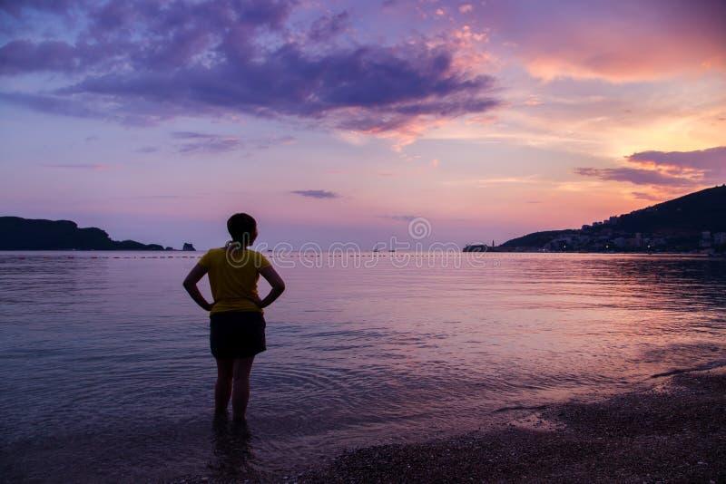 Klädd kvinna på Pebble Beach på soluppgång arkivbilder