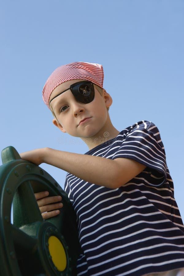 Klädd pojke som piratkopierar rymma ett styrninghjul arkivbild