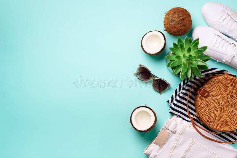Kläder för kvinnasommarlopp reser på blå bakgrund Jeans, gymnastikskor, bambupåse, solglasögon, kokosnöt och suckulent arkivbild