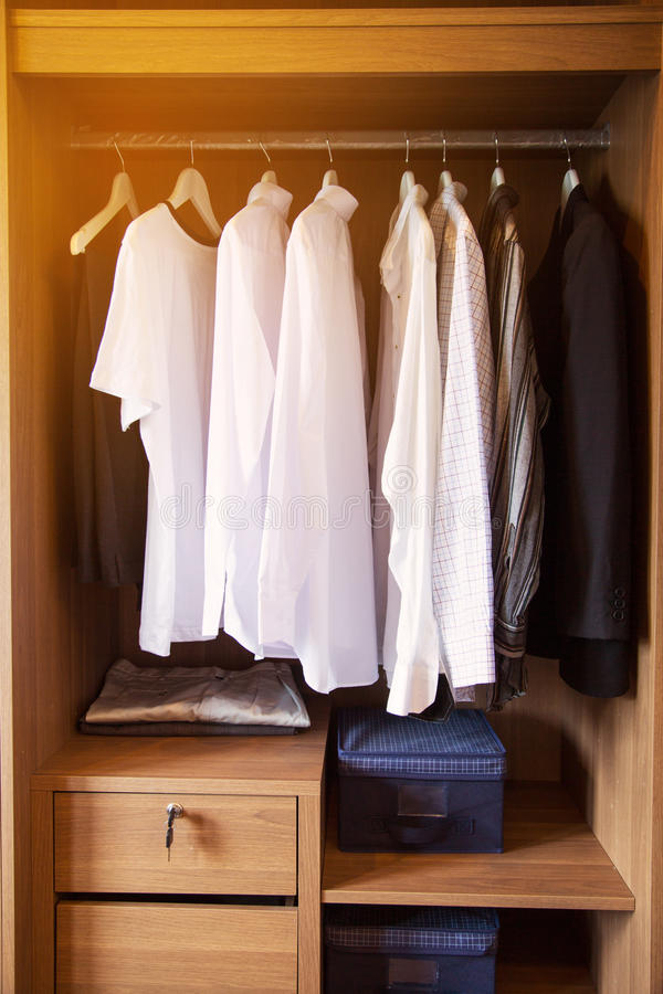 Kläder hänger på en hylla i ett lager för märkes- kläder, modern garderob med rad av kläder som hänger i garderob, tappningrum royaltyfria bilder