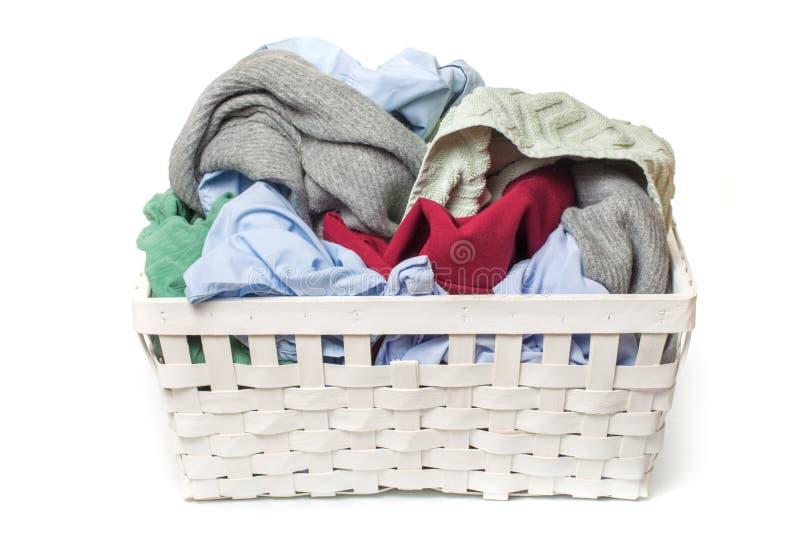 Kläder i tvätterien träkorg som isoleras på vit bakgrund royaltyfri foto