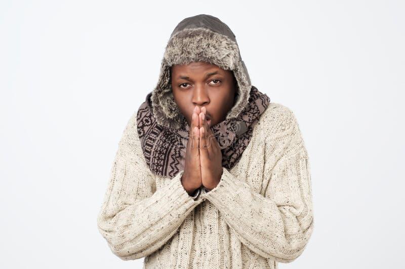 Kläder men känsla för vinter för afrikansk amerikanman som bärande är kalla i en vit bakgrund arkivfoto