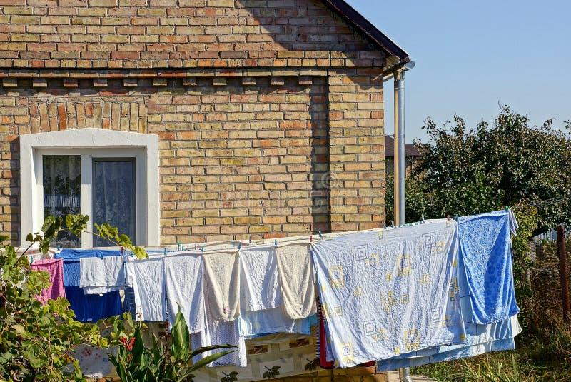 Kläder och linne torkar, når de har tvättat sig i gården nära väggen av huset arkivbild