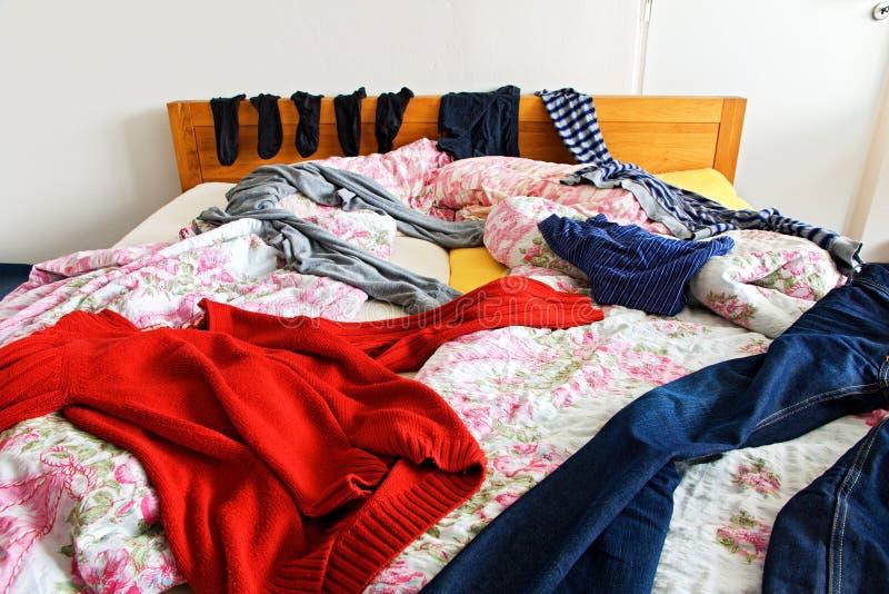 Kläder på sängen royaltyfri fotografi