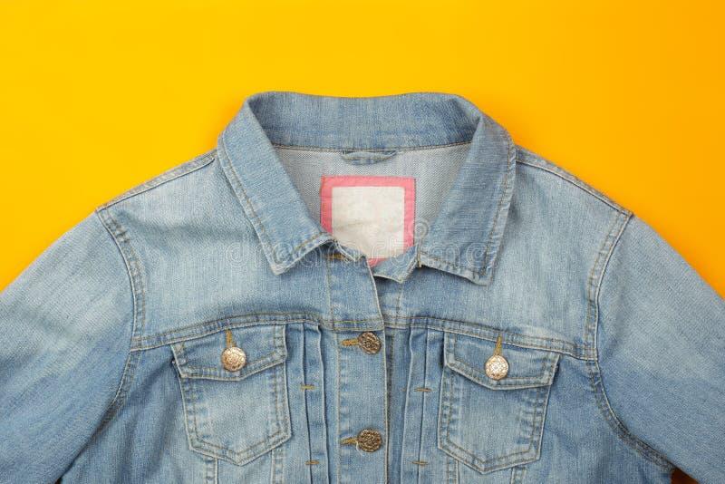 Kläder, skor och tillbehör - jeans för bästa sikt klår upp gul bakgrund arkivfoton