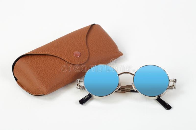 Kläder, skor och tillbehör - solglasögon och brunt fall royaltyfri fotografi