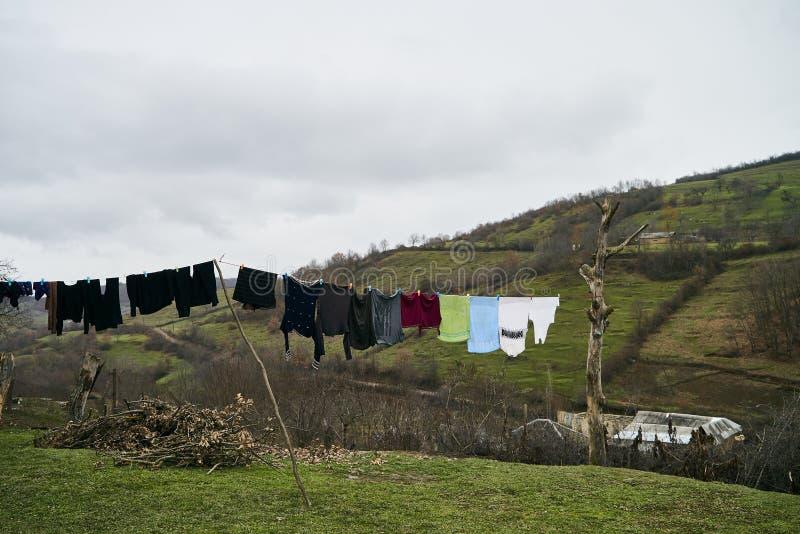 Kläder som hänger för att torka på en tvätterilinje arkivfoton