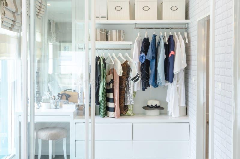 Kläder som hänger i garderob med hatten arkivbild