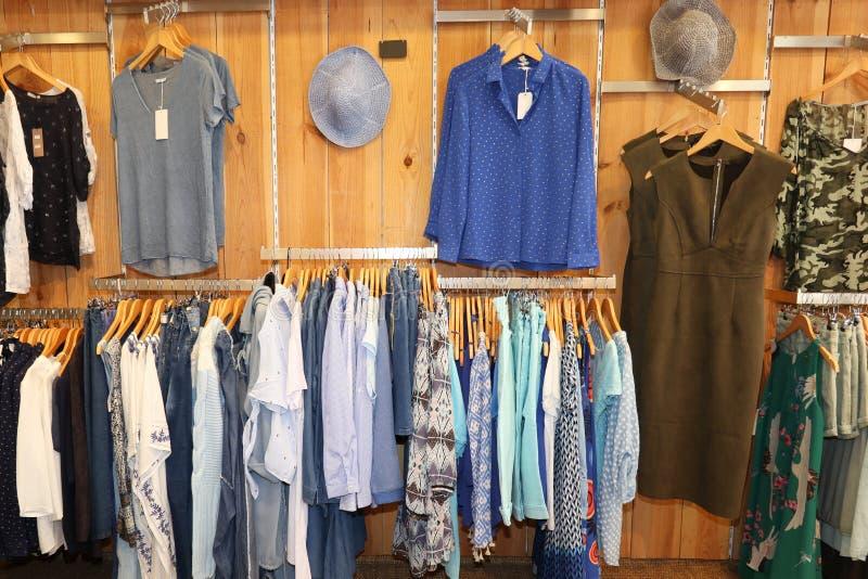kläder som hänger på kuggen i inre sikt för boutique av kvinnaklädlagret royaltyfria foton