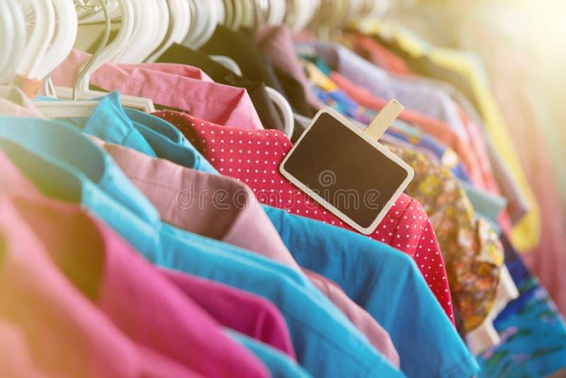 Kläder som hänger på kuggen i lagret arkivfoton