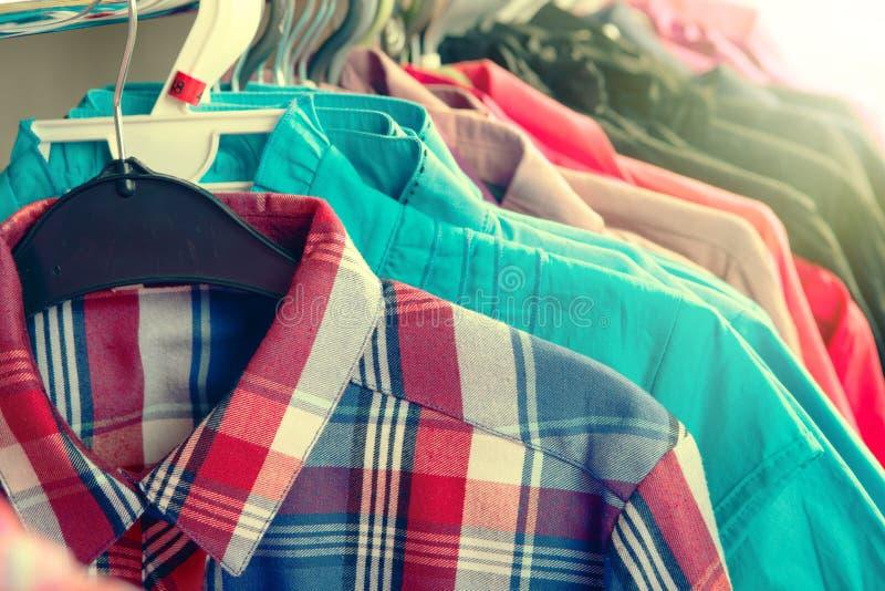 Kläder som hänger på kuggen i lagret royaltyfri foto