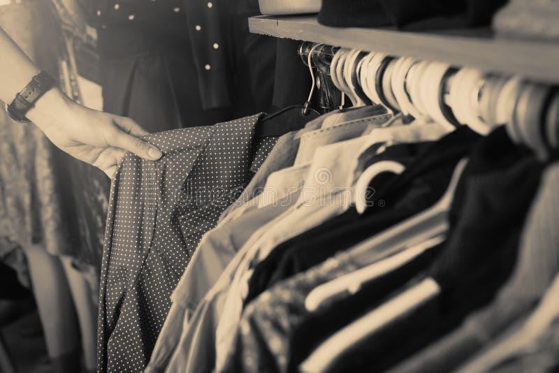 Kläder som hänger på kuggen i lagret arkivbild