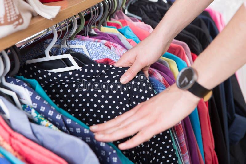 Kläder som hänger på kuggen i lagret royaltyfri fotografi