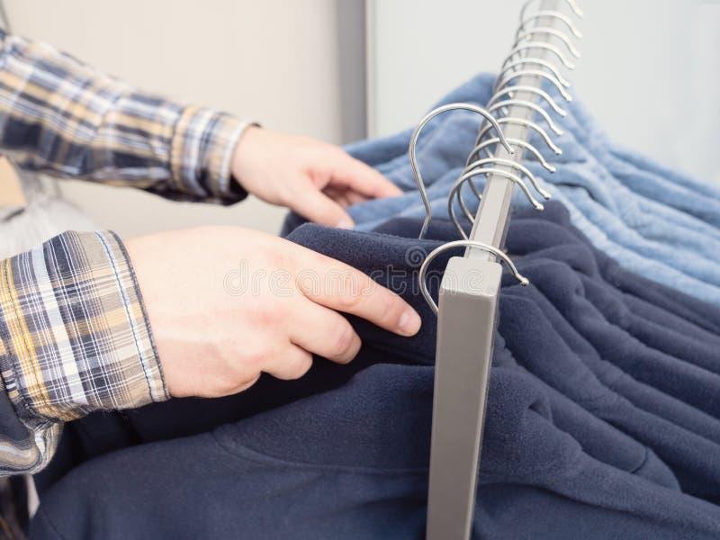Kläder som hänger på kuggen Manlig chiosing bär i kläderlager royaltyfria bilder