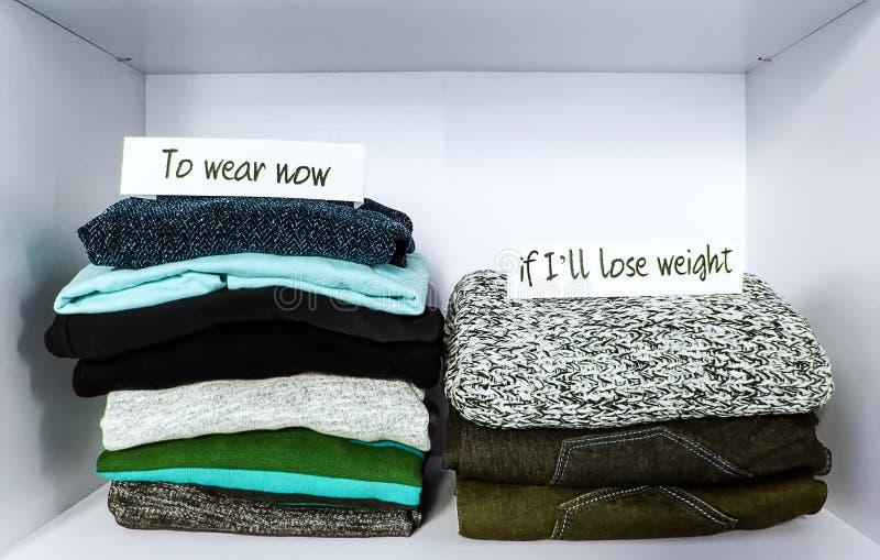 Kläder som sorterar i garderob på vit hyllabakgrund Att att bära nu, om I' ll förlorar pappers- anmärkningar för vikt fotografering för bildbyråer