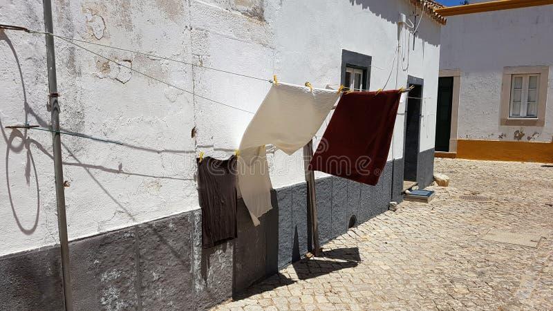 Kläder som torkar på en charmig kullerstengata för klädstreck i Faro, Portugal arkivbild